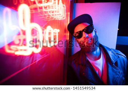 Hipster handsome man on the city streets being illuminated by neon signs. He is wearing leather biker jacket or asymmetric zip jacket with black cap, jeans and sunglasses. #1451549534