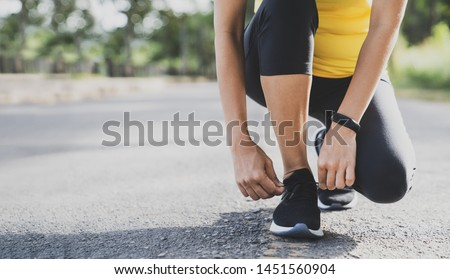 Running shoes runner woman tying laces for autumn run in forest park. Runner trying running shoes getting ready for run. Jogging girl exercise motivation heatlh and fitness. #1451560904