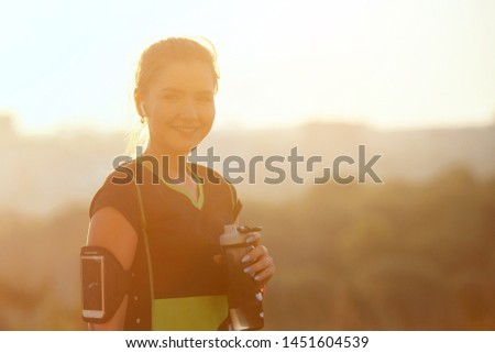 Woman resting after warm-up run with glass in hand at sunrise #1451604539