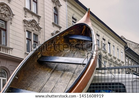 Transportation of large old boat on truck through the streets of Budapest. The bow of the boat protrudes above the cabin of the car in the background of the building with stucco. Selective focus. #1451608919