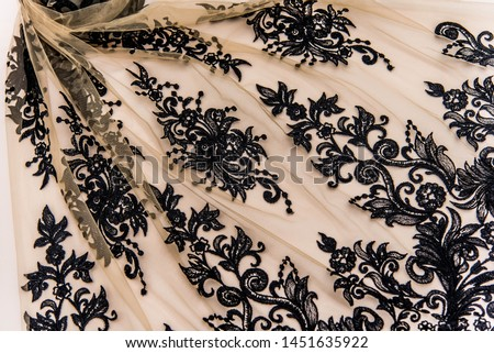 Texture lace fabric. lace on white background studio. thin fabric made of yarn or thread. a background image of ivory-colored lace cloth. Black lace on beige background. #1451635922