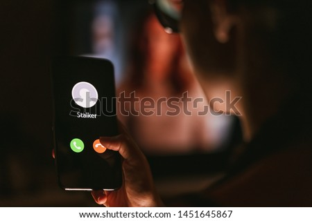 Phone call from a stalker late at night. Stalking or bullying with smartphone concept. Stalker caller, scammer or stranger. Woman answering to incoming call. Ex boyfriend with fake identity. #1451645867