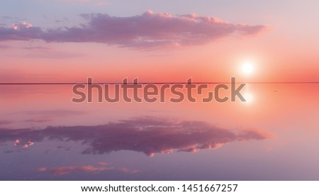 Landscape beautiful lilac sunset red sky solt lake saline Elton Baskunchak. The sun sets behind the horizon. The clouds are like the hands of a man holding the sun. Zen harmony, serenity, tranquility #1451667257