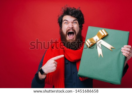 Photo of excited bearded guy, screaming and pointing at big box gift over red background #1451686658