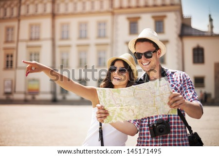Happy tourists sightseeing city with map Royalty-Free Stock Photo #145171495