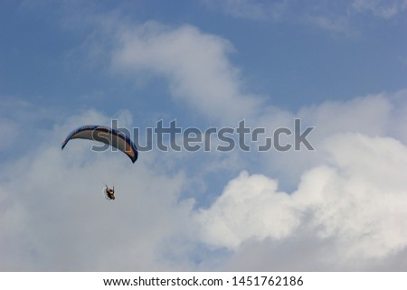 Paragliding pilots are flying over the clouds of Parangkusumo beach, Yogyakarta, Indonesia. February 17, 2018 #1451762186