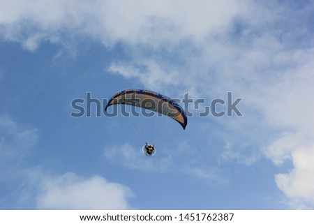 Paragliding pilots are flying over the clouds of Parangkusumo beach, Yogyakarta, Indonesia. February 17, 2018 #1451762387