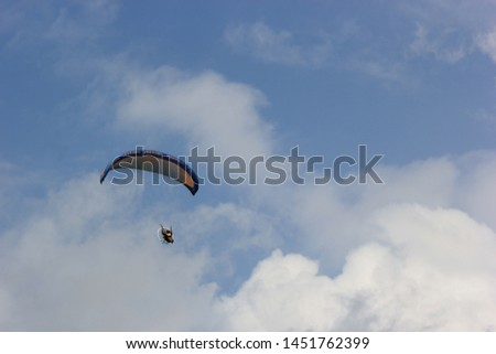 Paragliding pilots are flying over the clouds of Parangkusumo beach, Yogyakarta, Indonesia. February 17, 2018 #1451762399