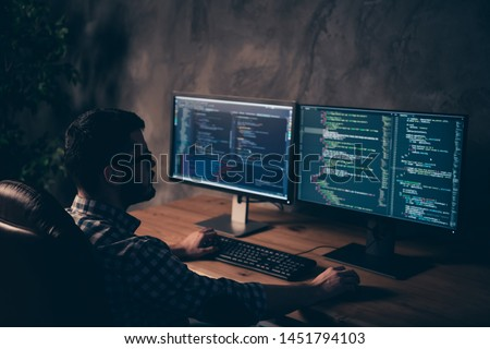Close up back rear behind photo handsome he him his guy coder typing keyboard development outsource IT processing language two monitors table office agency wear specs formalwear plaid shirt #1451794103
