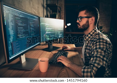 Close up side profile photo handsome he him his guy brainstorming briefing coder typing php css keyboard development outsource IT two monitors table office agency wear specs formalwear plaid shirt #1451794160