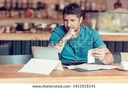 Restaurant owner checking monthly reports on a tablet, bills and expenses of his small business. Start-up entrepreneur concerned about financial reports #1451818145