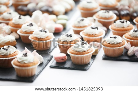 Beautiful multicolored decorated candy table baked sweet tasty cupcake cupcakes on a party, beautifully decorated catering banquet table with different candy sweet delicacy. #1451825093