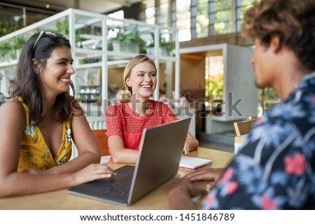 Candid lifestyle shot of three young trendy millennial diverse friends collaborating together on laptop computer in bright modern restaurant laughing