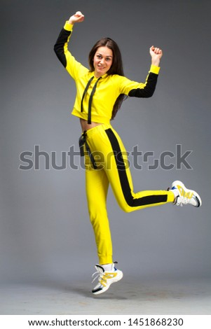 Portrait of a young beautiful brunette woman in yellow tracksuit, isolated on gray background #1451868230
