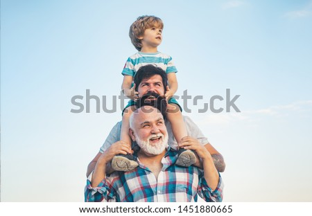 Men generation: grandfather father and grandson are hugging looking at camera and smiling. Fathers day concept. Generation concept. Weekend family play. Men in different ages #1451880665