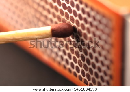Match rubbing with box to ignite the flame, side of the red box, making the match burn with friction. Fire off. Royalty-Free Stock Photo #1451884598