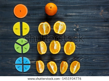 Сolorful math fractions and oranges as a sample on dark wooden background or table. Interesting creative funny math for kids. Education, back to school concept. Geometry and mathematics materials. #1451934776