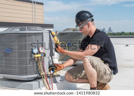 Hvac technician inspecting an condensing unit. Royalty-Free Stock Photo #1451980832