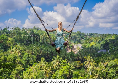 Young woman swinging in the jungle rainforest of Bali island, Indonesia. Swing in the tropics. Swings - trend of Bali #1451981690