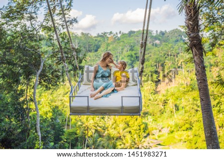 Mother and son swinging in the jungle rainforest of Bali island, Indonesia. Swing in the tropics. Swings - trend of Bali. Traveling with kids concept. What to do with children. Child friendly place #1451983271