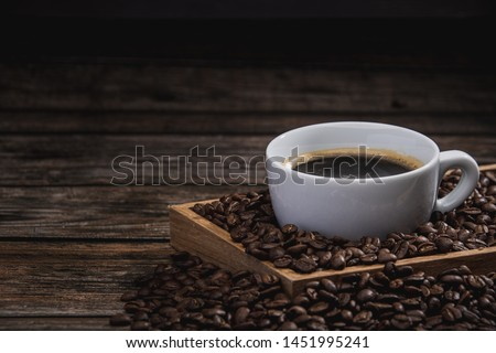 cup of coffee with beans on wooden table #1451995241