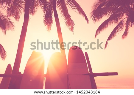 Surfboard and palm tree on tropical sunset beach background. Travel adventure sport and summer holiday vacation concept. Vintage tone filter effect color style.