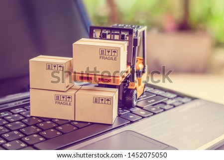 Logistics, supply chain and delivery service concept : Fork-lift truck moves a pallet with box carton. Boxes on a laptop computer, depicts wide spread of products around globe in ecommerce booming era #1452075050