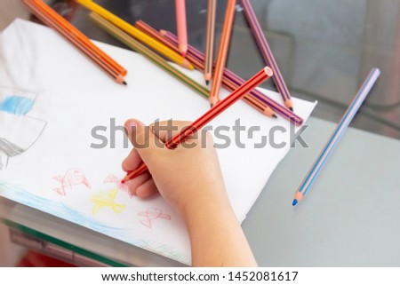 Child draws with colorful pencils. Children's drawing on theme of fishing with goldfish, car #1452081617