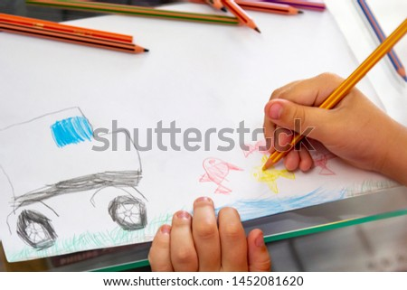 Child draws with colorful pencils. Children's drawing on theme of fishing with goldfish, car #1452081620