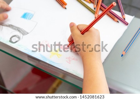 Child draws with colorful pencils. Children's drawing on theme of fishing with goldfish, car #1452081623