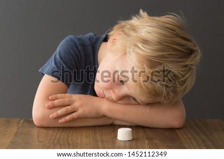 Cute child looks at single marshmallow on table. The marshmallow test/marshmallow experiment.  #1452112349