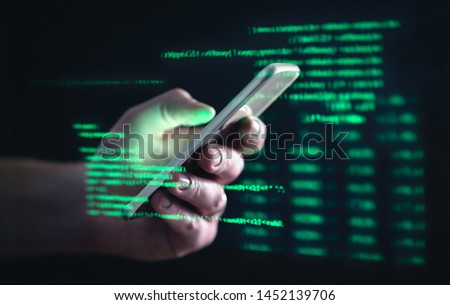 Darkweb, darknet and hacking concept. Hacker with cellphone. Man using dark web with smartphone. Mobile phone fraud, online scam and cyber security threat. Scammer using stolen cell. AR data code. Royalty-Free Stock Photo #1452139706