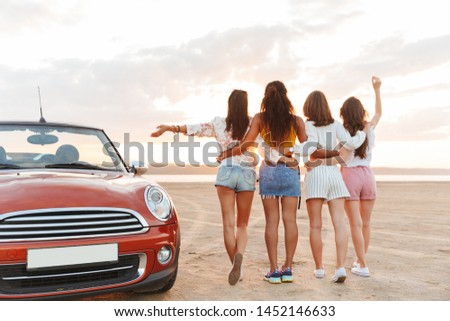 Back view picture of young girls friends walking near car outdoors at the beach with raised hands.