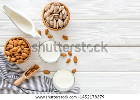 Healthy snack with almonds for milk on white wooden background top view mock up #1452178379