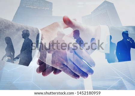 Close up of two businessmen shaking hands in modern city with double exposure of business people and network interface. Concept of connection and partnership. Toned image Royalty-Free Stock Photo #1452180959