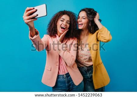 Dark-haired girls fooling around for photo. Studio shot of smiling young ladies enjoying shooting. #1452239063