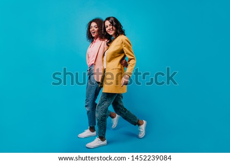 Active girls in casual outfit looking to camera. Mixed race women walking during photoshoot. #1452239084