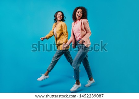 Two well-dressed young ladies posing in studio. Indoor full-length portrait of mixed race women. #1452239087
