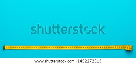 Top view of yellow soft measuring tape. Minimalist flat lay image of tape measure with metric scale over turquoise blue background. Panoramic orientation photo of tape measure with copy space. #1452272513