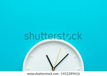 Part of white wall clock with yellow second hand hanging on wall. Close up image of plastic wall clock over turquiose blue background with copy space.