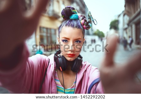 Cool funky young girl with headphones and crazy hair enjoy power of music taking selfie on street – hipster woman with trendy avant-garde look having fun - Music fan concept with playful carefree teen #1452292202