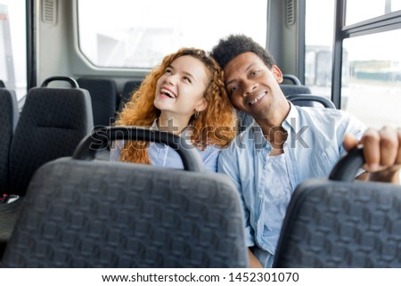 African guy with red-haired girl sitting in the bus laughing leaning on each other. Urban public transport #1452301070