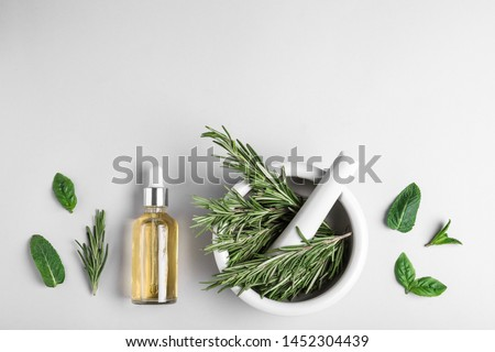 Flat lay composition with herbal essential oil and space for text on light background #1452304439