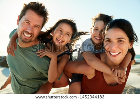 Mid adult white parents piggybacking their kids on a beach, smiling to camera, close up, backlit #1452344183