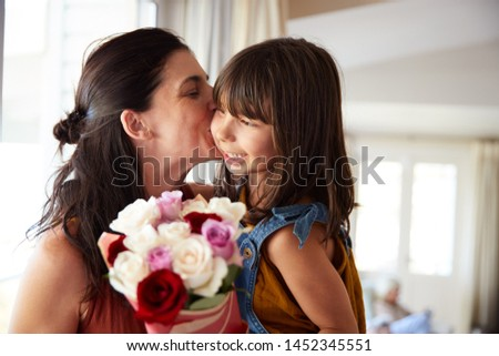 Mid adult woman kissing her daughter, who's given her a bunch of flowers on her birthday, close up #1452345551