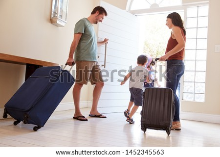 Mid adult white couple and kids leaving their home with luggage to go on vacation, full length Royalty-Free Stock Photo #1452345563