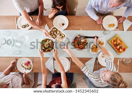 Three generation white family sitting at a dinner table together serving a meal, overhead view #1452345602
