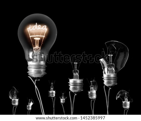 Group of hanging light bulbs with shining fiber in a shape of Idea concept isolated on black background #1452385997