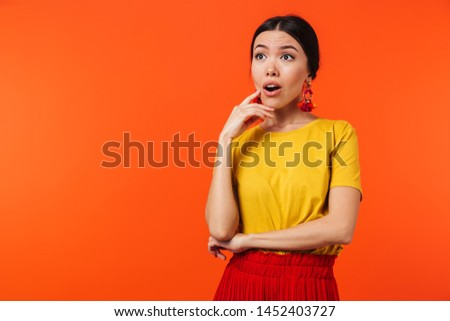 Image of a beautiful shocked young woman posing isolated over orange wall background. #1452403727