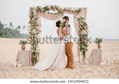 Bride and groom enjoying beach wedding in tropics, wedding arch, ocean background. Wedding ceremony on a tropical beach. Happy groom and beautiful bride kissing under the arch decorated with flowers  #1452404021